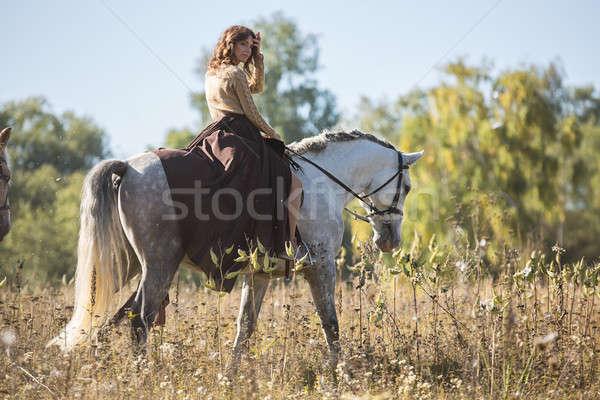 Gyönyörű lány lovaglás fehér ló mező profil kamerába Stock fotó © bezikus