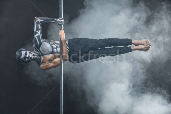 Male pole dancer posing in dark studio Stock photo © bezikus