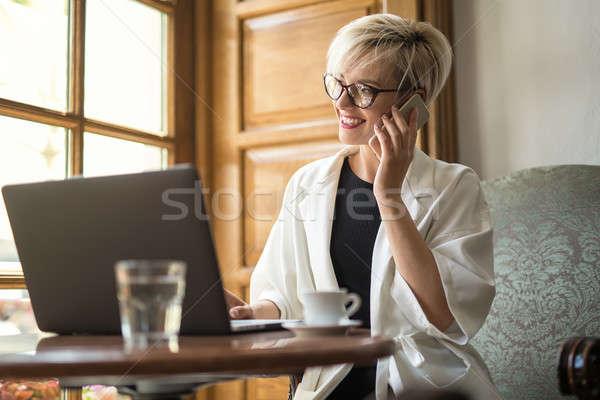 Girl talks on cell in cafe Stock photo © bezikus