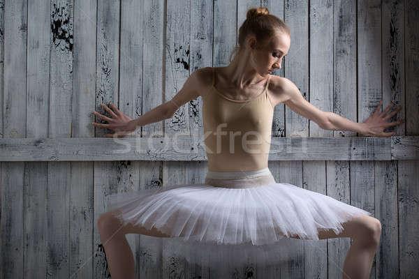Ballerina standing near a wooden wall on pointe Stock photo © bezikus