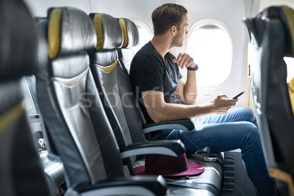 Knap vent vliegtuig venster mobieltje handen Stockfoto © bezikus