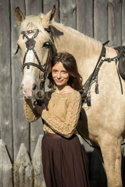 Young attractive girl is walking with his horse Stock photo © bezikus