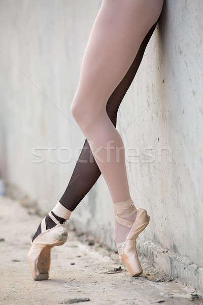 Ballerina feet close-up on a background of textured concrete wal Stock photo © bezikus