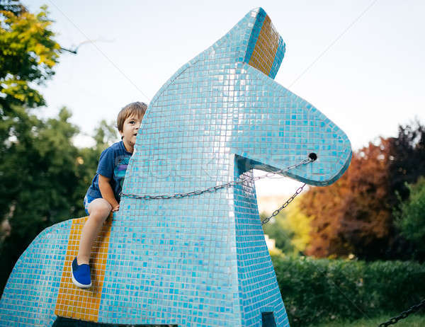 Little boy riding a toy horse ceramic tile Stock photo © bezikus