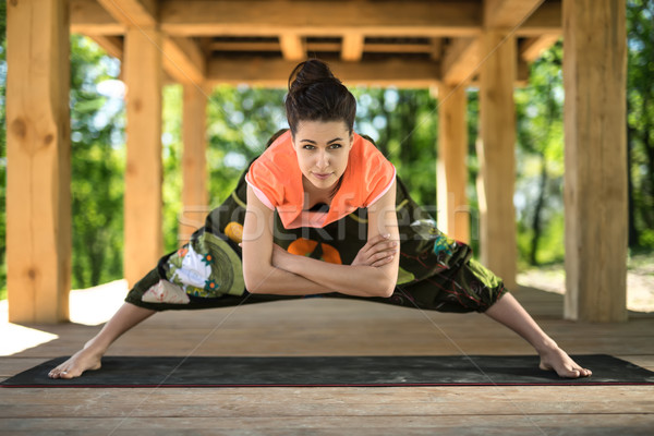 Girl makes wide-legged forward bend Stock photo © bezikus