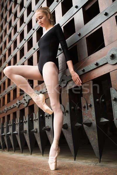 Slim dancer stands on one leg near the old gate Stock photo © bezikus