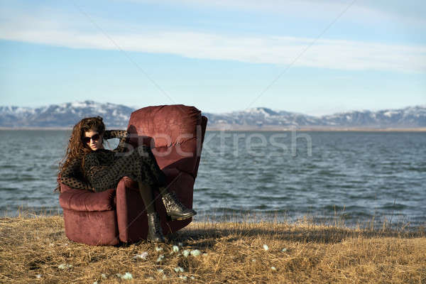 Girl sits on armchair outdoors Stock photo © bezikus