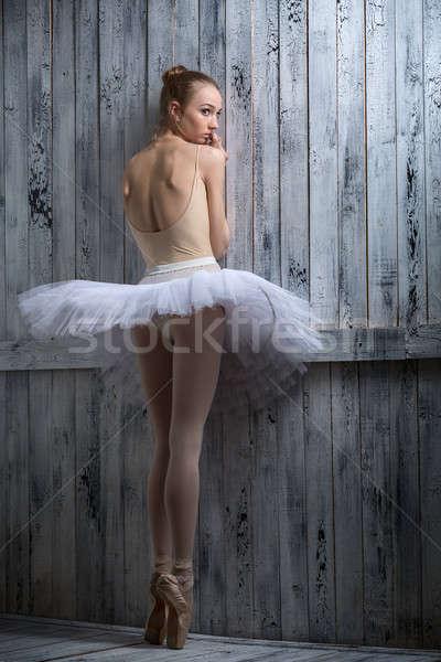 Modest ballerina standing near a wooden wall Stock photo © bezikus