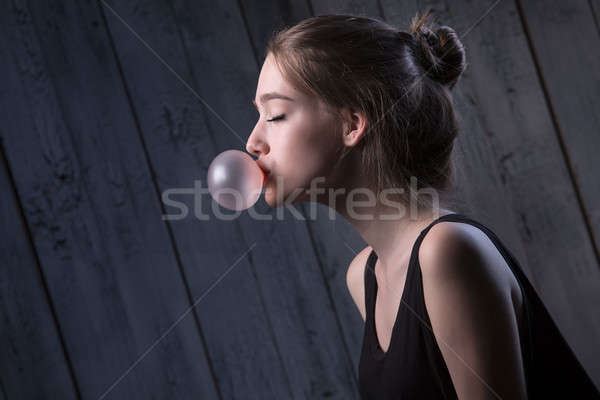 Girl with pink bubble of chewing gum Stock photo © bezikus