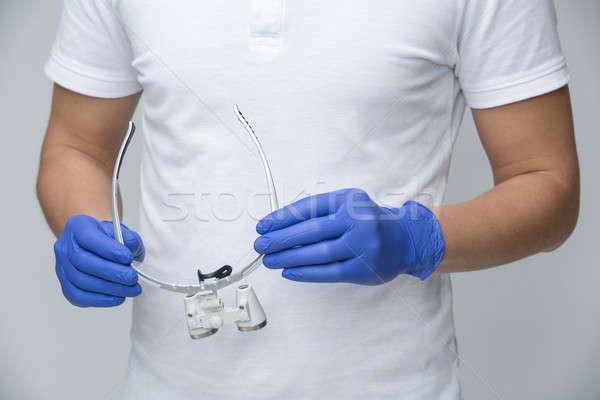 Doctor holding the binocular loupes Stock photo © bezikus