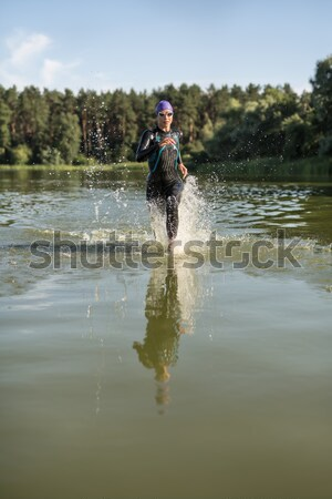 Athletic girl runs on the water Stock photo © bezikus