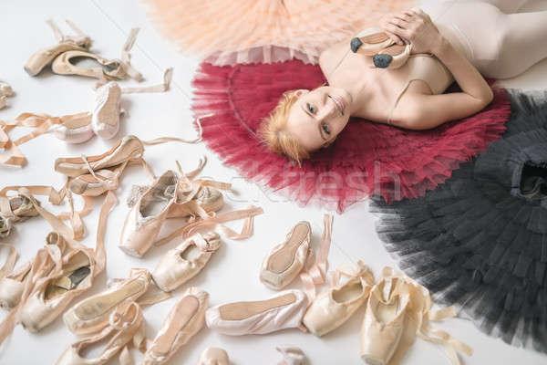 Smiling ballerina lies on the colorful tutus on the white floor  Stock photo © bezikus