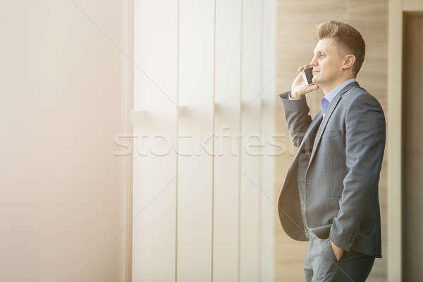 Cute hombre de negocios traje negro pie espacioso Windows Foto stock © bezikus
