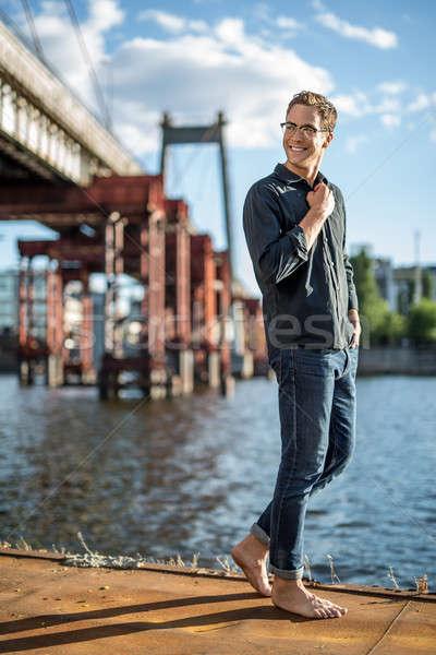 босиком парень улыбаясь очки реке Сток-фото © bezikus