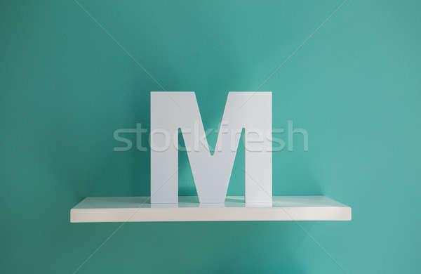 Letter M turquoise color on a white shelf. Stock photo © bezikus