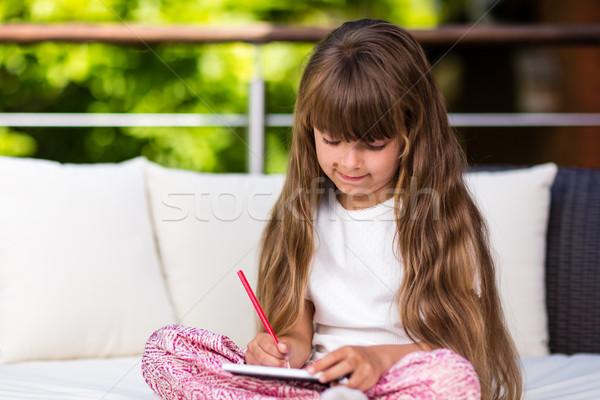 Girl with long hair writing at notepad Stock photo © bigandt