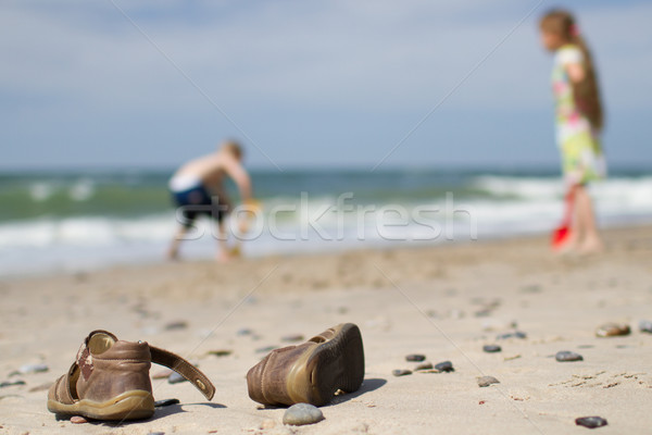 Stock photo: Kids sandals and children at the beach