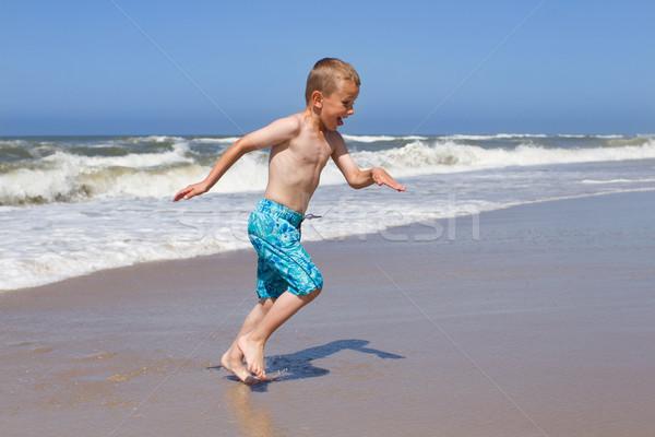 Boy fleeing a wave at sandy beach Stock photo © bigandt