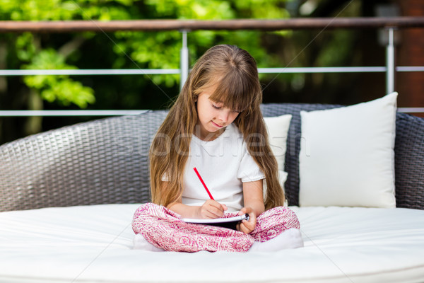 Girl sitting on patio with notepad Stock photo © bigandt