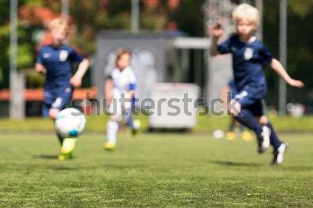 Tre giovani ragazzi giocare calcio verde Foto d'archivio © bigandt