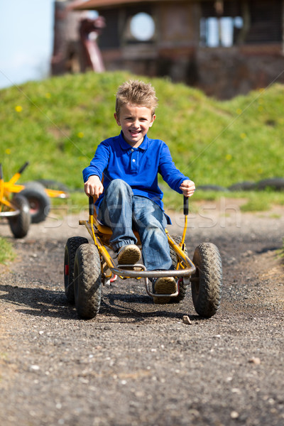 Caucasian boy having fun in moon buggy Stock photo © bigandt
