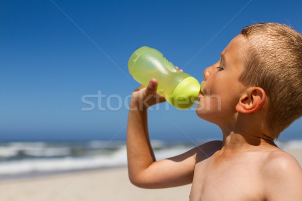Stock photo: Thirsty boy drinking from water bottle