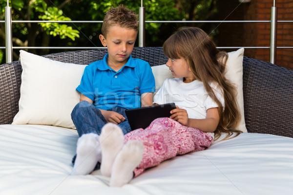 Gyerekek osztás tabletta fiú lány ül Stock fotó © bigandt