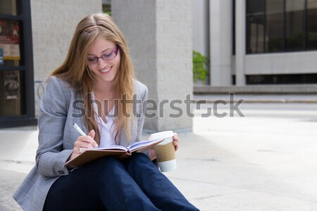 Beautiful, smiling woman writing in her journal Stock photo © bigjohn36