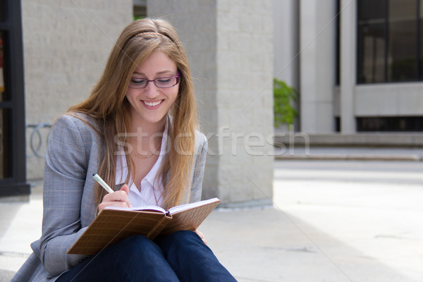 Happy woman writing in her journal Stock photo © bigjohn36