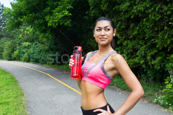 Fit young woman with water bottle after running Stock photo © bigjohn36