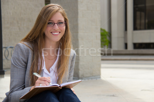 Cheerful, attractive young woman with journal Stock photo © bigjohn36