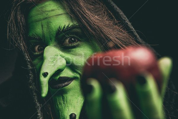 Evil witch looking at camera holding a red apple Stock photo © BigKnell