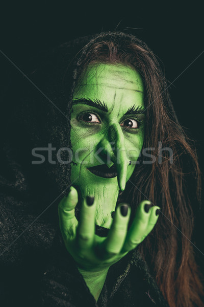 Evil witch holding an invisible item Stock photo © BigKnell