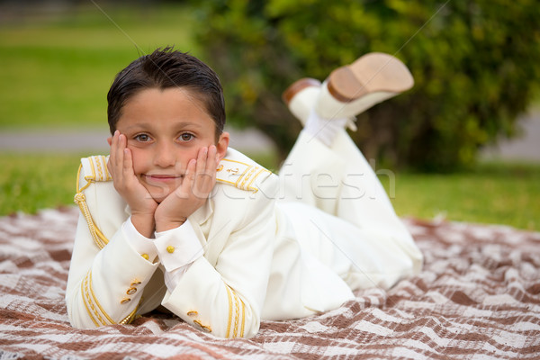 Young First Communion boy lying on a blanket over the grass Stock photo © BigKnell