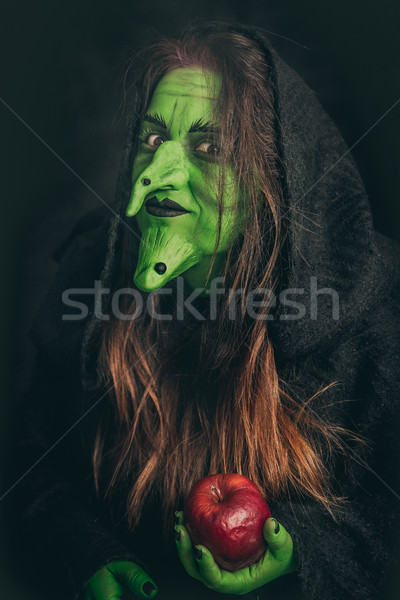 Evil witch holding a rotten apple Stock photo © BigKnell