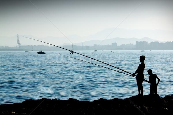 Siluet erkek balık tutma şehir su çocuk Stok fotoğraf © BigKnell