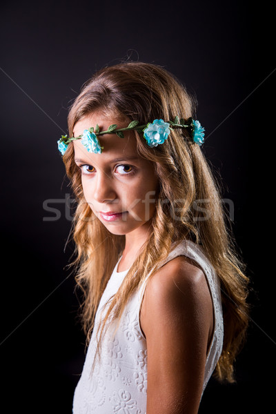 Young girl with flower tiara and sober look on black background Stock photo © BigKnell