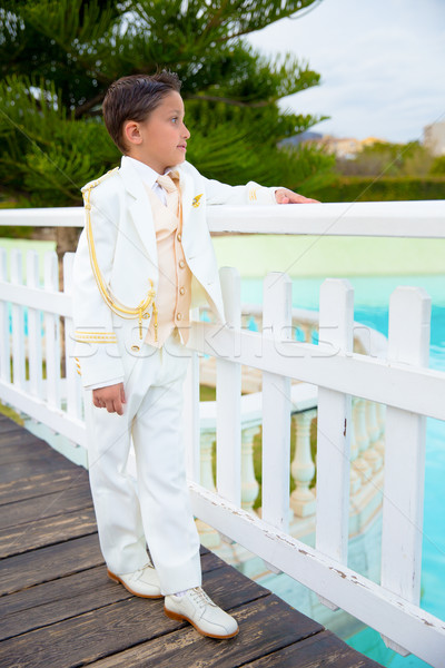 Young First Communion boy leaning on a white wooden fence over a Stock photo © BigKnell