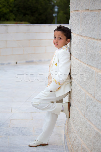 Young First Communion boy leaning on a wall with  one foot Stock photo © BigKnell