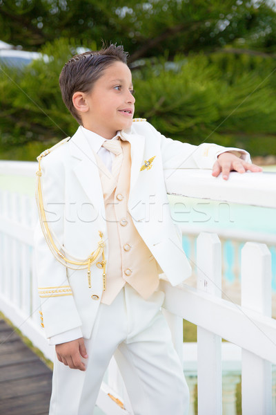 Young First Communion boy leaning on a white wooden fence Stock photo © BigKnell