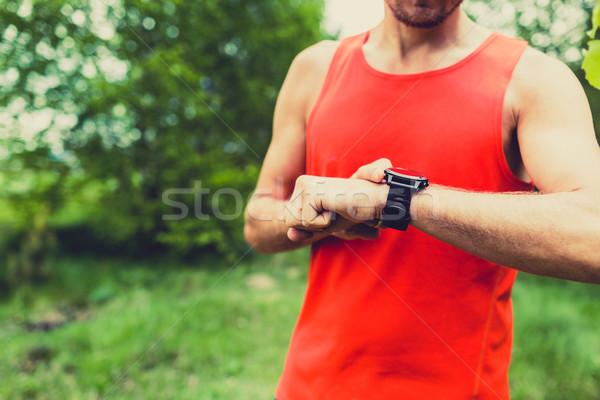 Runner looking at sport watch smartwatch Stock photo © blasbike