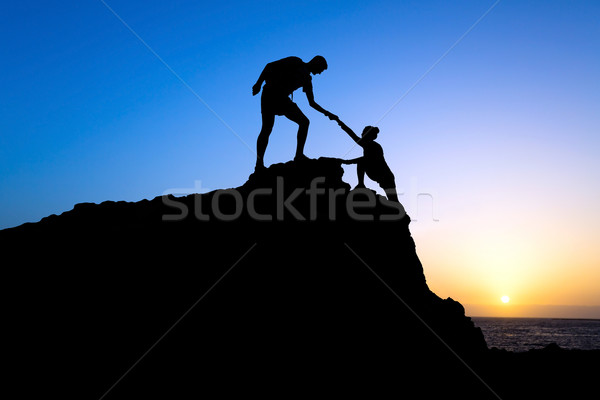 Man and woman help silhouette in mountains Stock photo © blasbike