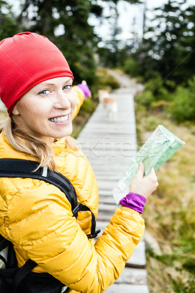Woman hiking and reading map in forest Stock photo © blasbike