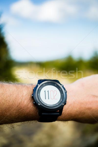 Runner on mountain trail looking at stopwatch, activity tracker Stock photo © blasbike