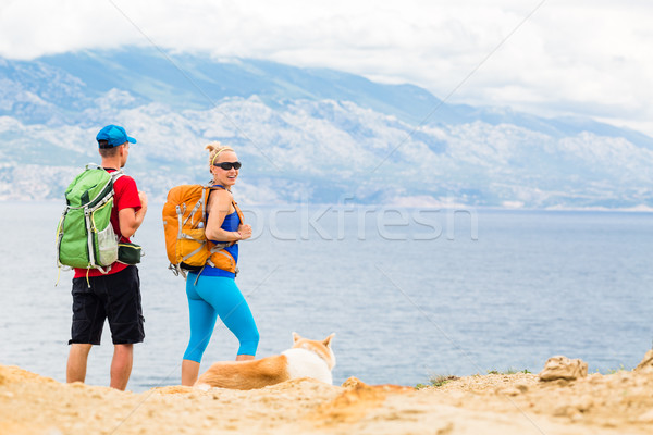 Couple hikers walking with dog at seaside and mountains Stock photo © blasbike