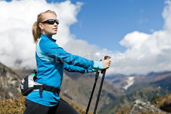 Woman nordic walking and exercising in mountains Stock photo © blasbike