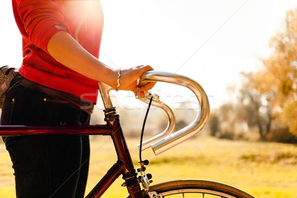 Kadın bisiklete binme bisiklet sonbahar park gün batımı Stok fotoğraf © blasbike
