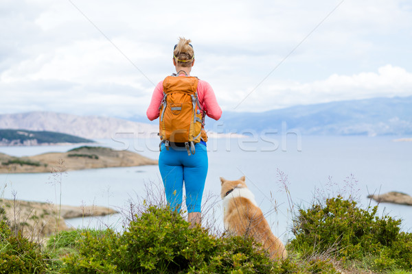 Woman hiking walking with dog on seaside trail Stock photo © blasbike