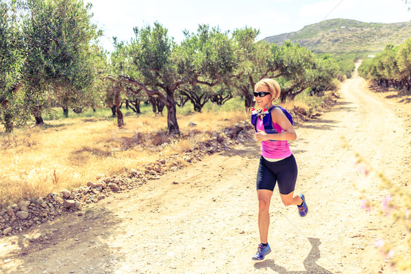 Stock photo: Happy woman trail running in beautiful mountains