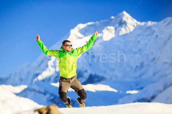 Homem andarilho feliz saltar inverno montanhas Foto stock © blasbike